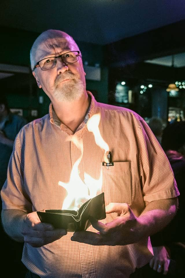 Man telling story with a book on fire