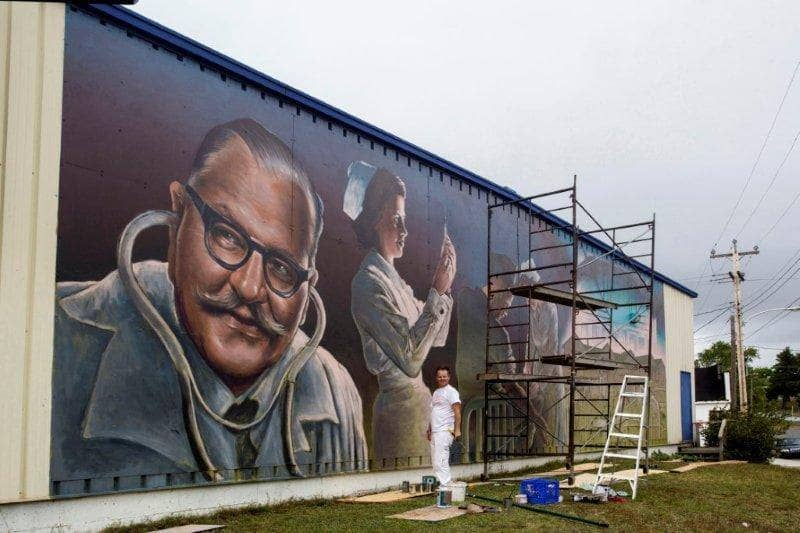 Pulse Of The Community mural in Botwood, with muralist Charlie Johnston at work