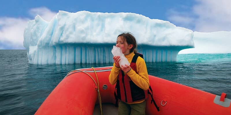 girl in boat near iceberg
